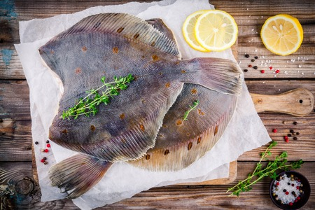 Raw flounder fish, flatfish on wooden background Reklamní fotografie