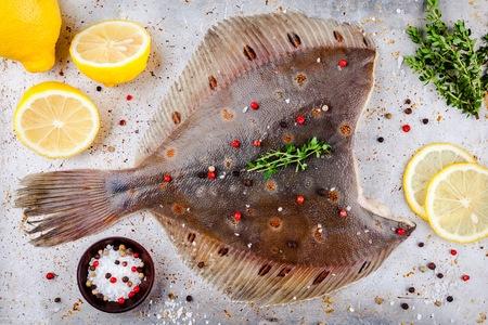 bakground: Raw flounder fish, flatfish on rustic background
