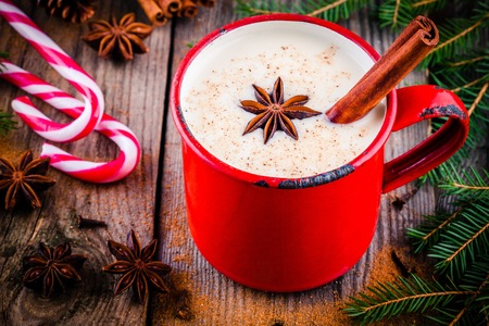 Christmas drink: eggnog with cinnamon and anise in red mug on wooden rustic background Reklamní fotografie
