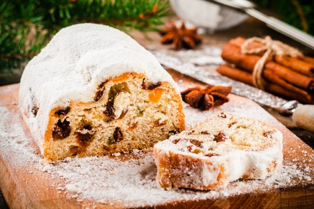 Traditional christmas stollen fruit cake on wooden rustic background