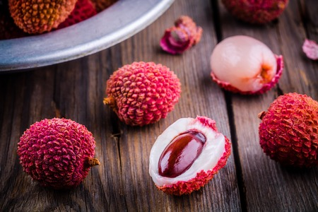 litchee: Fresh organic lychee fruit in a bowl on a rustic wooden background