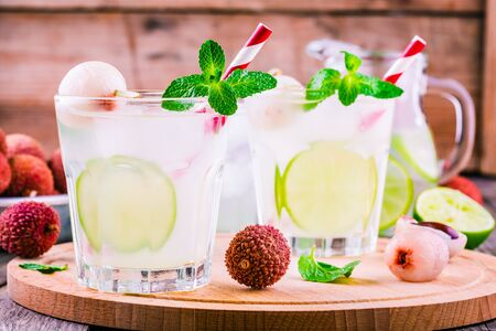 Cold fresh lemonade with lychee, lime and mint in glass on wooden table
