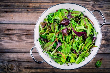 Fresh salad with mixed greens in colander on wooden background