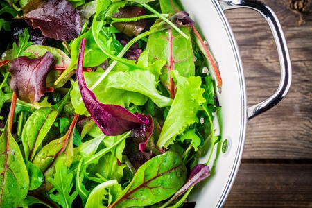 Fresh salad with mixed greens in colander on wooden background closeup Stock Photo