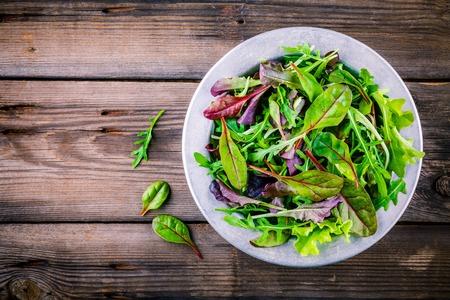 木製の背景上のボウルにミックス グリーンのサラダ 写真素材