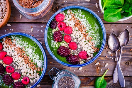 Green spinach smoothie bowl with raspberry, blackberry, flax seeds, sunflower seeds and coconut chips on wooden background