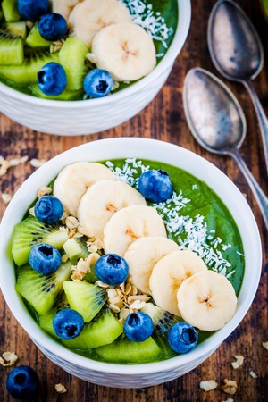 Green smoothie bowl with banana, kiwi, blueberry, granola and coconut on wooden background Stock Photo