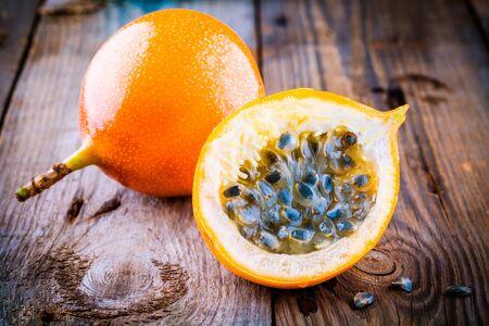 grenadilla: Organic raw ripe yellow granadilla passion fruit on wooden background