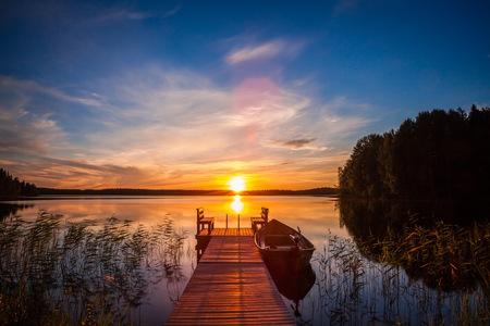 Tramonto sul molo di pesca al lago in Finlandia rurale Archivio Fotografico - 76630957