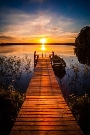 Puesta de sol sobre el muelle de pesca en el lago en Finlandia rural