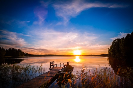 made in finland: Sunset over the fishing pier at the lake in rural Finland