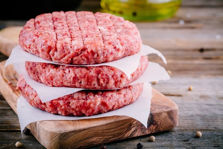 Ingredients for burgers: raw minced beef cutlets on wooden background