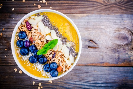 Yellow smoothies bowl with blueberries, granola, chia seeds and almonds on wooden background