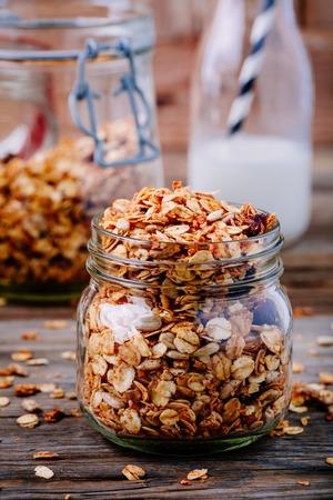 sunflower seeds: Healthy breakfast homemade granola in glass jar on wooden background Stock Photo