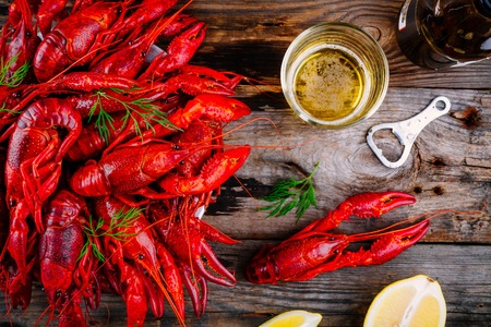 Boiled crayfish with dill and beer on wooden background
