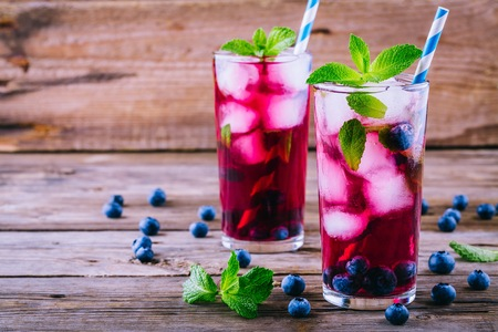Blueberry ice sangria with  mint in glasses on wooden background