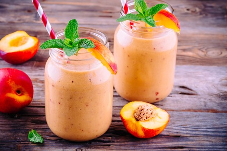 Healthy nectarine smoothies in a mason jar with mint on wooden rustic background