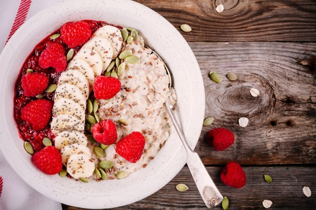 Healthy breakfast: porridge with fresh raspberries, banana, flax seeds and pumpkin seeds on wooden background