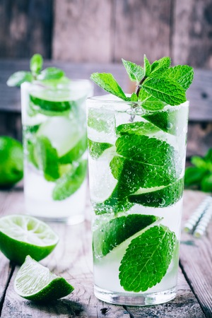 fresh mojito cocktails with lime, mint and ice in glass on wooden background Stock Photo