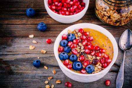 banana: Healthy summer breakfast mango  smoothie bowl with granola, blueberries, pomegranate and chia seeds on wooden background