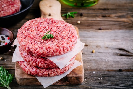 Raw ground beef meat burger steak cutlets on wooden background