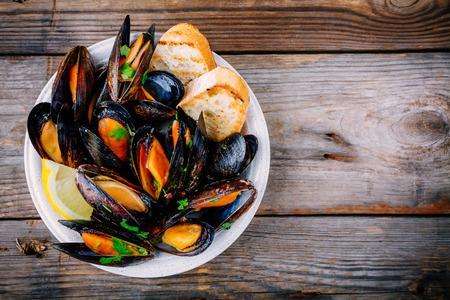 おいしい魚介のムール貝をソースとパセリで添えて。 レモンとバゲット。貝のアサリ。 トップビュー。