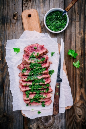 Sliced grilled barbecue beef steak with green chimichurri sauce on wooden background