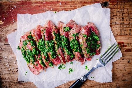 angus: Sliced grilled barbecue beef steak with green chimichurri sauce on wooden background
