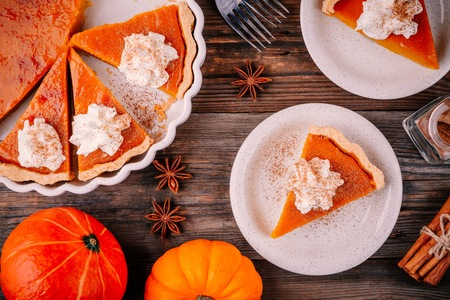 Homemade Pumpkin Pie for Thanksgiving with whipped cream and cinnamon on rustic background Stock Photo