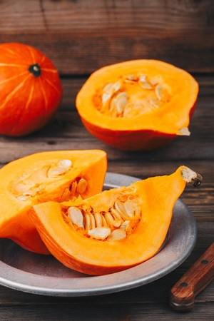 fresh raw pumpkin slices with seeds on a wooden background. Stock Photo