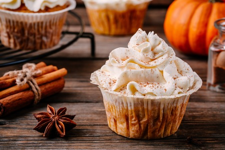 Pumpkin cupcakes decorated with cream cheese frosting on wooden background