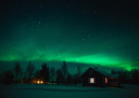 Northern lights (Aurora Borealis) over snowed-in cottage in Lapland village. Finland Redakční