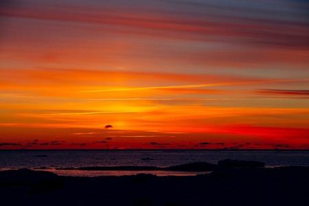 Winter nature landscape. Sunset over frozen sea, Finland. Stock Photo