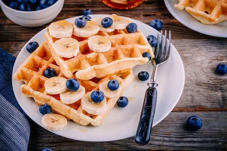 Fresh homemade belgian waffles with blueberries and banana for breakfast on wooden background.