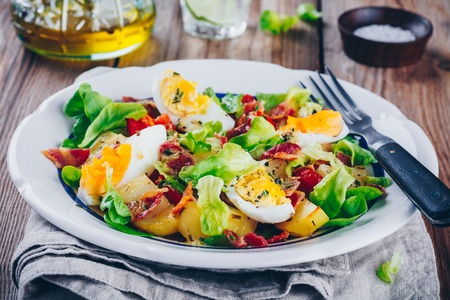 potato salad with eggs, green lettuce, cherry tomatoes and bacon
