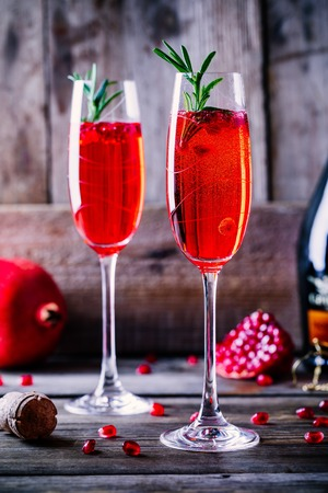 Pomegranate champagne mimosa cocktail with rosemary in glasses on wooden background Stock Photo