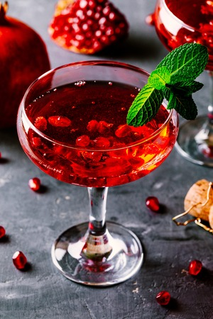 red cocktail with champagne and pomegranate seeds on rustic background