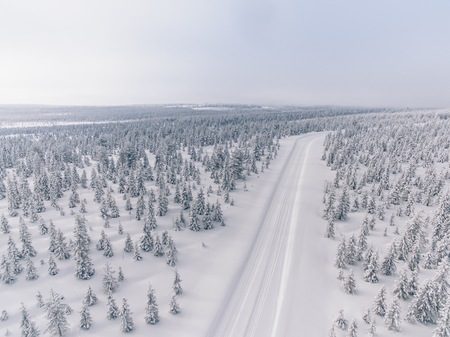 Aerial view of the road in the winter snow forest in Finland, Lapland