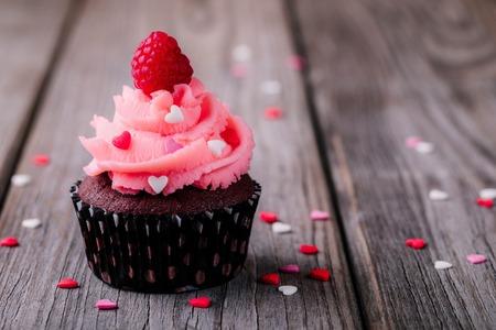 バレンタインデーのためのピンクのクリーム、砂糖のハートと新鮮なラズベリーとチョコレートカップケーキ 写真素材 - 92998161