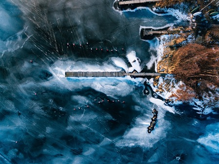 Aerial view of the winter frozen lake with wooden piers from above captured with a drone in Finland.