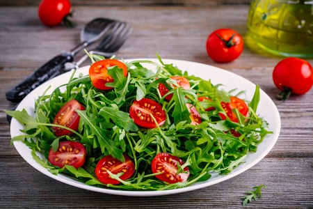 fresh green salad with arugula and red tomatoes on rustic wooden background Stock Photo