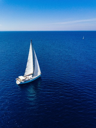 Aerial birds eye view from drone of white yacht in deep blue sea Stockfoto
