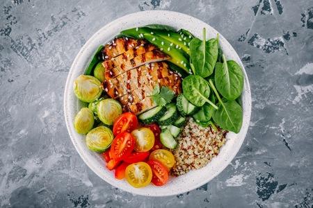 Almuerzo saludable tazón de Buda con pollo a la parrilla, quinua, espinacas, aguacate, coles de Bruselas, tomates, pepinos sobre fondo gris oscuro. Vista superior.