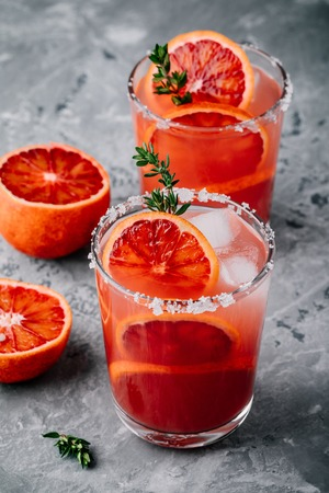 Blood Orange Margarita cocktail with ice and thyme on dark backgorund