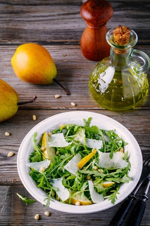 green salad bowl of arugula with pear, parmesan cheese and pine nuts on a wooden background Stock Photo