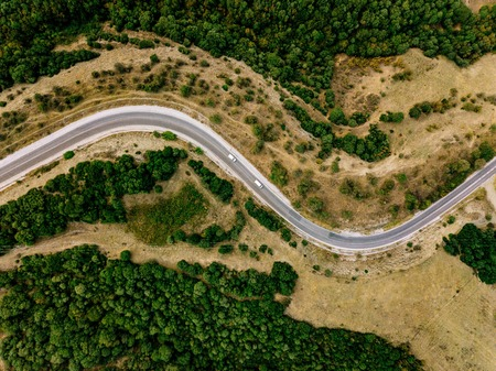 Aerial above view of a rural landscape with a curvy road running through it in Greece. Drone photography