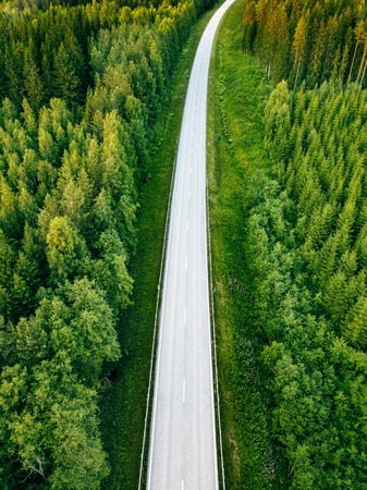 Aerial view from above of country road through the green summer forest in summer Finland. drone photography Banco de Imagens