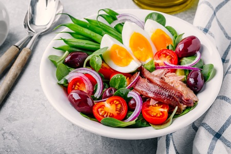 nicoise salad with tuna, anchovies, eggs, green beans, olives, tomatoes, red onions and salad leaves on gray background