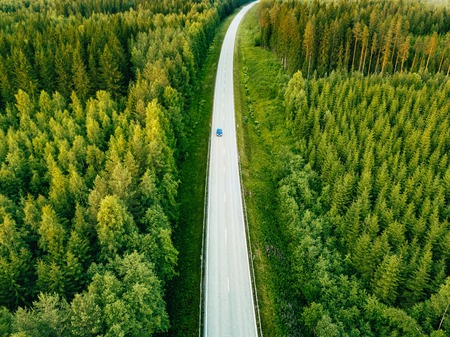 Aerial view from above of country road through the green summer forest in summer Finland. drone photography Standard-Bild
