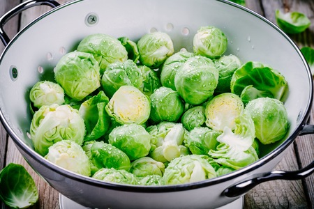 Fresh organic Brussels sprouts in a colander on a wooden table